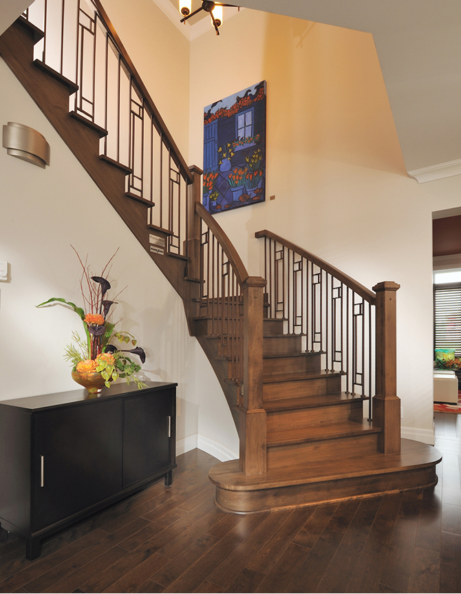 Half-turn wood staircase with forged steel balusters