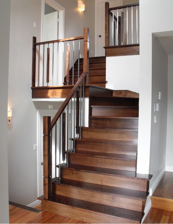 Wooden staircase with wood, metal, and forged steel balusters