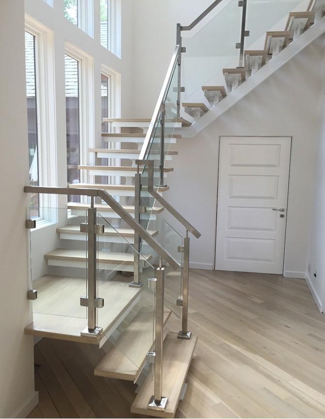 Escalier avec limon central en acier, garde-corps en verre et barreaux en acier inoxydable