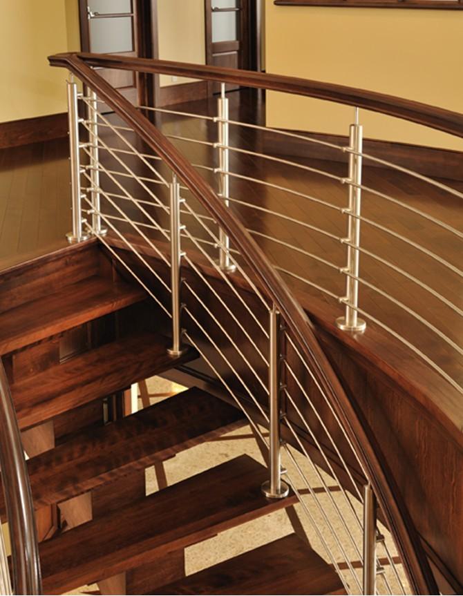 Escalier courbe avec marches en bois et poteaux et tiges en acier inoxydable