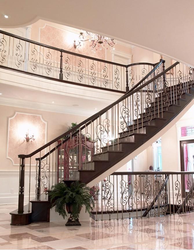 Escalier courbe en bois avec barreaux en acier forgé